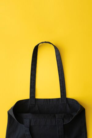 Empty open cotton eco black shopping bag on yellow background with copy space, top view. Vertical Foto de archivo
