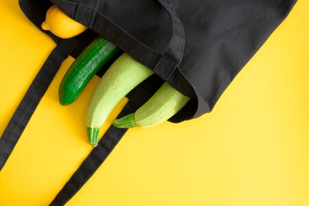 Cotton eco black bag with zucchini, cucumber and lemon on yellow background with copy space, top view. Concept zero waste and healthy lifestyle, horizontal