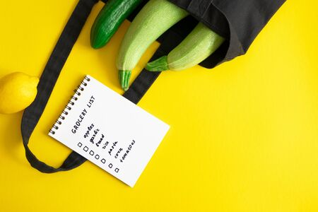 Grocery list in paper notepad and cotton eco black bag with zucchini and cucumber, lemon on yellow background with copy space, above. Concept dietary and healthy lifestyle, horizontal