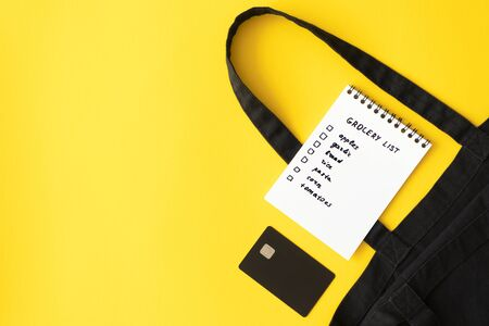 Grocery list in paper notepad, cotton eco black shopping bag and credit card on yellow background with copy space, top view. Concept online purchases product, horizontal Foto de archivo