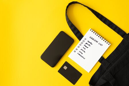 Smartphone, credit card, grocery list in paper notepad and cotton eco black shopping bag on yellow background with copy space, top view. Concept online purchases product, horizontal Foto de archivo