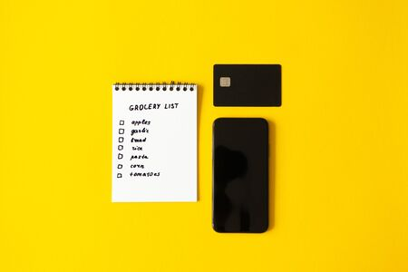 Smartphone, credit card, grocery list in paper notepad on yellow background with copy space flat lay, top view. Concept online purchases product, horizontal Foto de archivo