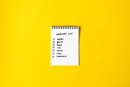 Grocery list paper notepad on yellow background with copy space, top view