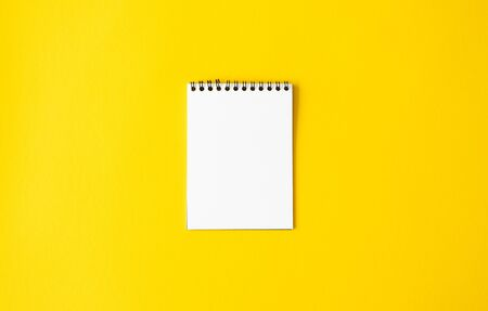 Empty white paper spiral notepad on yellow background. Mockup memo or diary, top view. Minimalistic reminder Foto de archivo