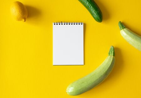 Empty white paper notepad, zucchini, lemon and cucumber on yellow background with space for text. Mockup memo recipe or meal plan, top view Foto de archivo