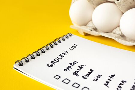 Close-up grocery list in paper notepad with selective focus on yellow and eggs on background