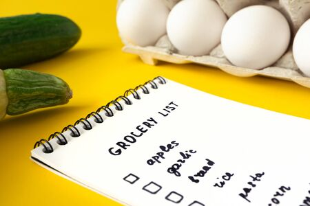 Close-up grocery list in paper notepad with selective focus on yellow and products on background