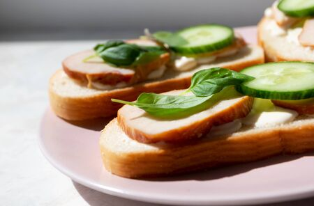 Close-up on sandwich with ham, basil leaves and cucumber. Details of food