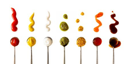 Ketchup, mustard, mayonnaise, basil pesto, sweet chili sauce and teriyaki soy sauce in spoon isolated on white background, top view. Various seasoning and dip border horizontal banner format