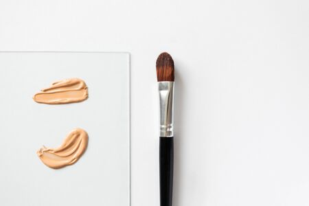 Beige liquid creamy foundation smears on glass and make-up brush on white background, top view. BB cream or CC cream sample smudge, above Stock fotó