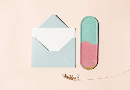 Blue mail envelope, blank white paper letter, dry herb and empty colorful concrete decor plate on beige background. Flat lay, top view. Summer, autumn concept. Wedding invitation template
