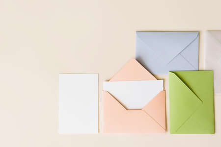 Mockup blank letter inside pink envelope, empty white paper and colorful closed envelopes on beige background, top view. Greeting card concept with copy space. Universally invitation template Banque d'images