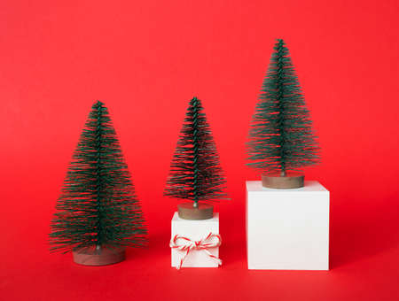Three decorative fir trees stay on white cube podium, Christmas gift box on red background. Winter holidays modern template for poster, banner, greeting card or invite