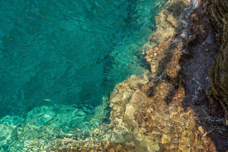 seawater: Gradient color from turquoise seawater to light brown rocky seabed. Photo was taken parallel to the horizon. Stock Photo