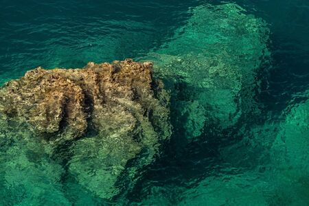 seawater: Gradient color from turquoise seawater to light brown rocky seabed. Photo was taken at an angle of 60 degrees to the horizon.