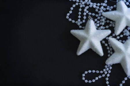 crystalline: Three white stars and crystalline beads on the painted black background.