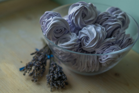 stays: Violet marshmallow in a large glass bowl with lavender flowers in front,   stays on a wooden table
