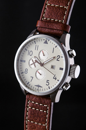 stitched: Mans metal wristwatch with calendar and brown leather stitched wristlet on black background, logos removed. Stock Photo