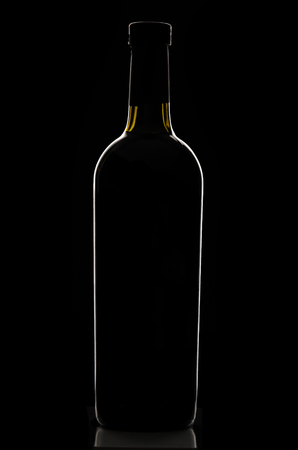 Stylish elegant black corked wine bottle reflected and outlined by light on black background. Logos removed.