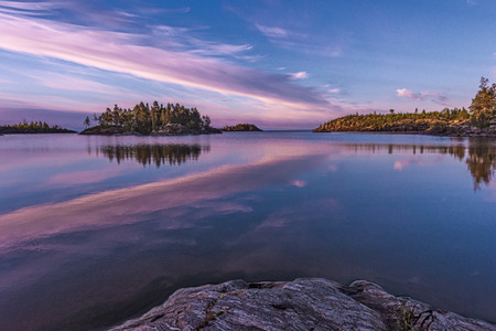 Beautiful sunrise in uninhabited place. Pink clouds that look like a giant pink feathering are reflected in the Ladoga lake, located in Karelia, north of Russia.