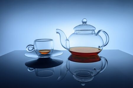 Studio image of transparent glass cup and teapot set with small amount of golden brown black tea at the bottoms of teapot and cup. Set is reflected in table. Graduated blue background.