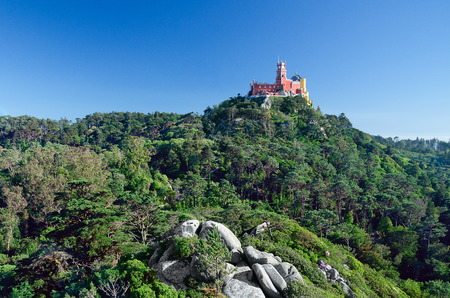 Pena Palace. It stands on the top of a hill in the Sintra Mountains above the town of Sintra, Portugal. It is a national monument and popular tourist place. One of the Seven Wonders of Portugal.