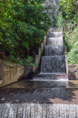 Man made waterfall with clean water running down the cascade concrete structure. Part of ecology friendly irrigation system of Madeira island, Portugal. Picture taken during summer season, in daylight.