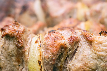 Close-up of few just roasted hot pieces of meat and onion.  This barbecue and picnic dish called shashlik is traditional for many countries. Unfocused meat at background. Copy space. Imagens