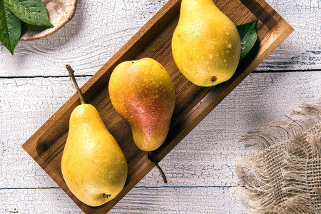 Yellow pears with leaves covered by water drops on square bamboo plate on old white wooden table with burlap napkin from one side. Selective focus. View from above. Healthy eating concept. Stok Fotoğraf