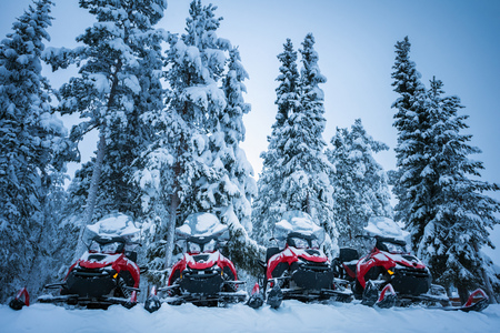 Four brightly colored red and black snowmobiles near Lapland forest. Vehicles parked in line near high firs in Lapland, Finland. Heavy snow on trees and ground. Winter seasonal landscape.