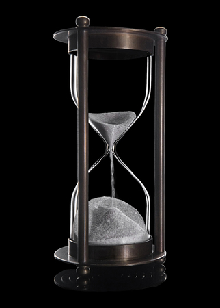 Elegant and stylish bronze vintage sandglass with trickling white sand. Object is Isolated with its reflection on black background. Pressed for time, hurry up, last minute, no time concepts.