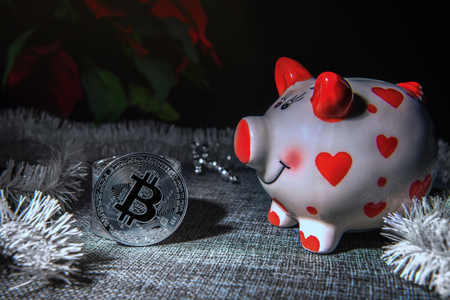 Greeting card with silver colored bitcoin coins, pig money bank, Christmas decor and copy space. Selective focus. Unfocused Christmas star plant at background. Investment and savings concepts.