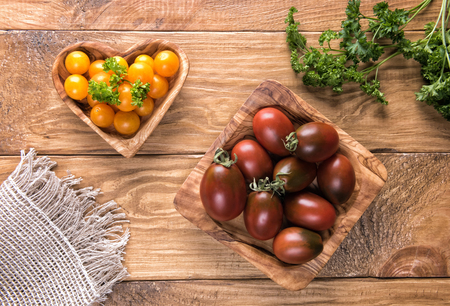 Dark red or black and yellow cherry tomatoes in natural wooden olive tree bowls on textured wooden table surface with green parsley leaves and burlap napkin. Healthy eating and dieting concept Stok Fotoğraf