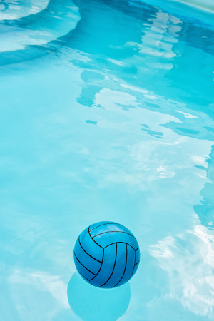 Child's blue ball on water surface in blue pool. Stairs are visible through clean water where sky and surroudings are reflected. Summer atmospere and private safety on water concepts. Copy space. Stock Photo