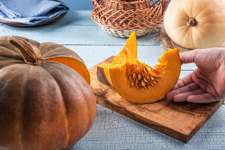 Human hand taking fresh, brightly colored pumpkin slices from cutting board near orange pumpkin. Blue wooden surface. Selective focus. Unfocused background. Healthy eating and autumn harvest concepts