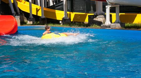 Happy boy in blue pool. Boy is surronded by water splashes in after riding down the colorful water structure on yellow inflatable ring. Laughing teenager is enjoying summer weekend in amusement park.