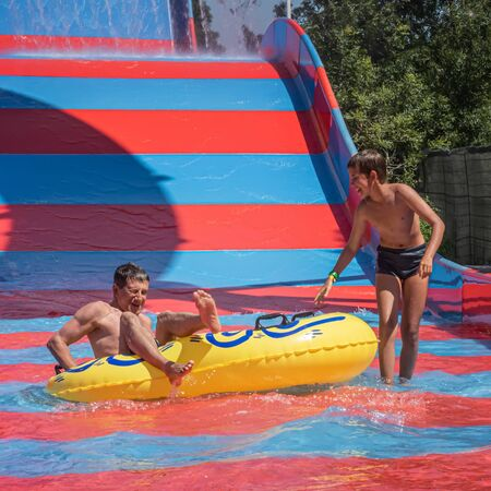 Square image of happy smiling family of father and son at amusement park. Adult and teenager boy are enjoying weekend together, just after riding down the water slide in yellow inflatable double ring. Banco de Imagens