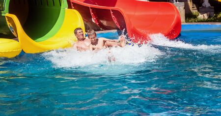 Family just after riding down the water park slide in yellow inflatable ring surrounded by water splashes. Father and son are enjoying summer weekend together at aquapark. Happy family concept.