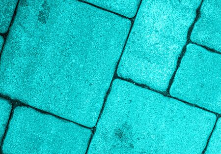 Detailed close-up of street pavement background with diagonal geometric pattern made of various square blocks. Textured rough surface toned in electric light blue color. View from above. Copy space.