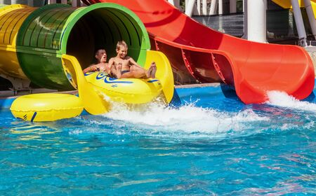 Family is riding down the water park structure, sitting together at inflatable ring and surrounded by water splashes. Father and son, adult and teenager boy are enjoying weekend together at aquapark.
