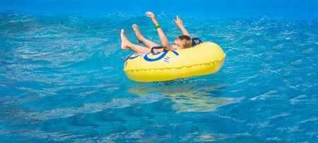 Happy boy in swimming pool. Boy is alone, swimming in yellow inflatable ring and surronded by water splashes. Wet teenager is enjoying summer weekend in amusement water park. Banner with copy space