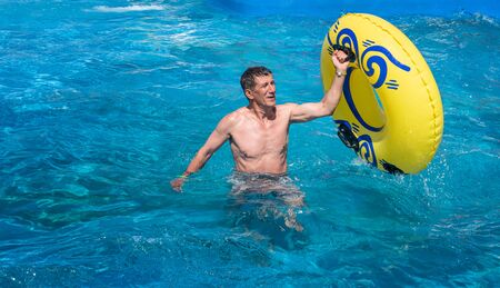 Happy man is enjoying summer weekend in amusement water park. Retired but still active adult in his sixties getting out of swimming pool while holding yellow inflatable ring in one hand. Copy space. Stok Fotoğraf