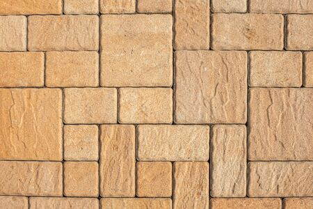 Highly detailed street pavement background with geometric pattern made of square blocks of different sizes with textured rough surface in brown and beige colors. View from directly above. Copy space.
