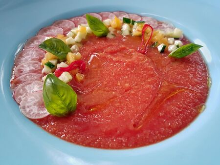 Close-up of restaurant served refreshing Spanish gazpacho soup made of red tomatoes, served in white plate and decorated with fresh vegetables and basil leaves. Healthy eating and dieting concept. Imagens