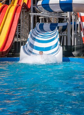 Laughing family of father and son at amusement park. Adult and teenager boy are both in huge water splash after riding down the water slide. Enjoying family weekend together concept. Copy space. Stock Photo