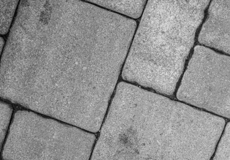 Detailed close-up of street pavement background with diagonal geometric pattern made of various square blocks. Textured rough surface in black and white. View from above. Copy space. Stockfoto