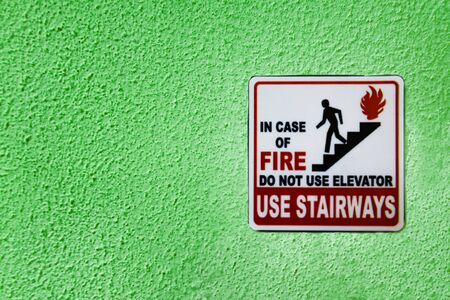 Red, black and white caution sign with person running from fire by stairs and warning not to use elevator in case of fire and to use stairs instead. Sign is on green textured wall surface. Copy space.