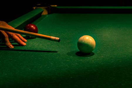 Wooden cue supported by adult male fingers while aiming at white ball on green table. Americal billiard cue sport, leisure and hobby activity. Cool vacation concept. Background with copy space. 免版税图像
