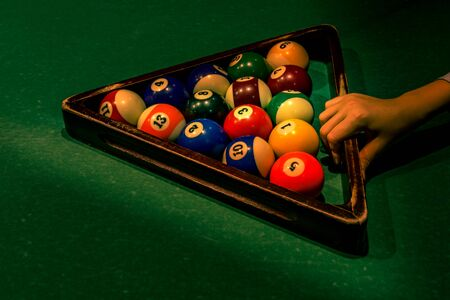 Teenager boys hand is holding wooden triangle with set of colorful numbered balls on green table. Getting ready for Americal billiard cue sport game, leisure and hobby activity. Cool vacation concept