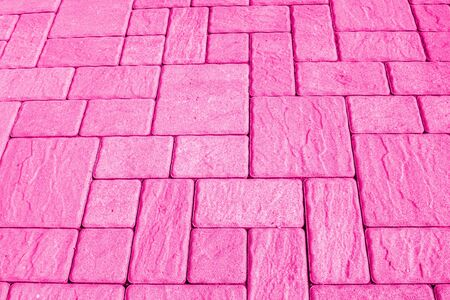 Geometric horizontal bright pink background with artificial stone paving made of square blocks of different shapes and sizes. Perpendicular and parallel lines. Toned image, high angle view, copy space